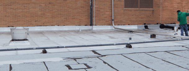 Roofer applying chemical on industrial roof