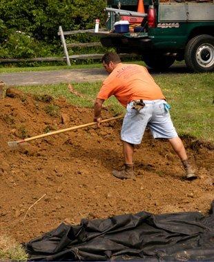Man doing excavation in the backyard using a garden rack