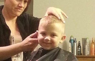 Happy kid getting his haircut