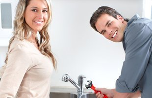 Woman and plumber smiling