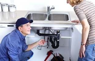 Plumber showing the sink pipes to a woman