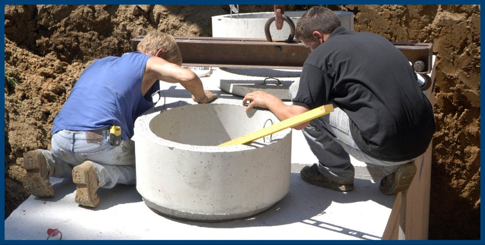 Plumbers installing a septic tank