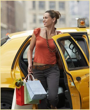 Smiling young woman with shopping bags exiting a yellow taxi