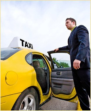 Man in a suit opening the door of a yellow taxi