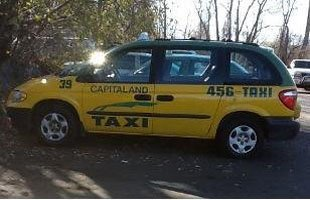 Man disembarking taxi while looking away