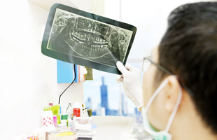 Portrait of male dentist checking dental x-ray at the office