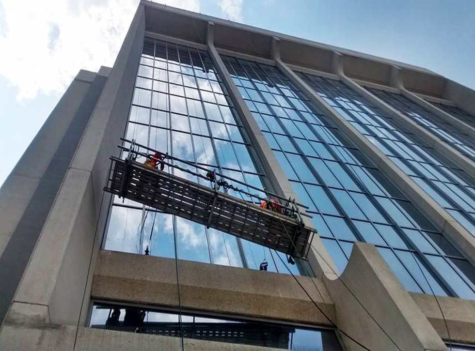 Outside of building with windows being cleaned by workers up on scaffold