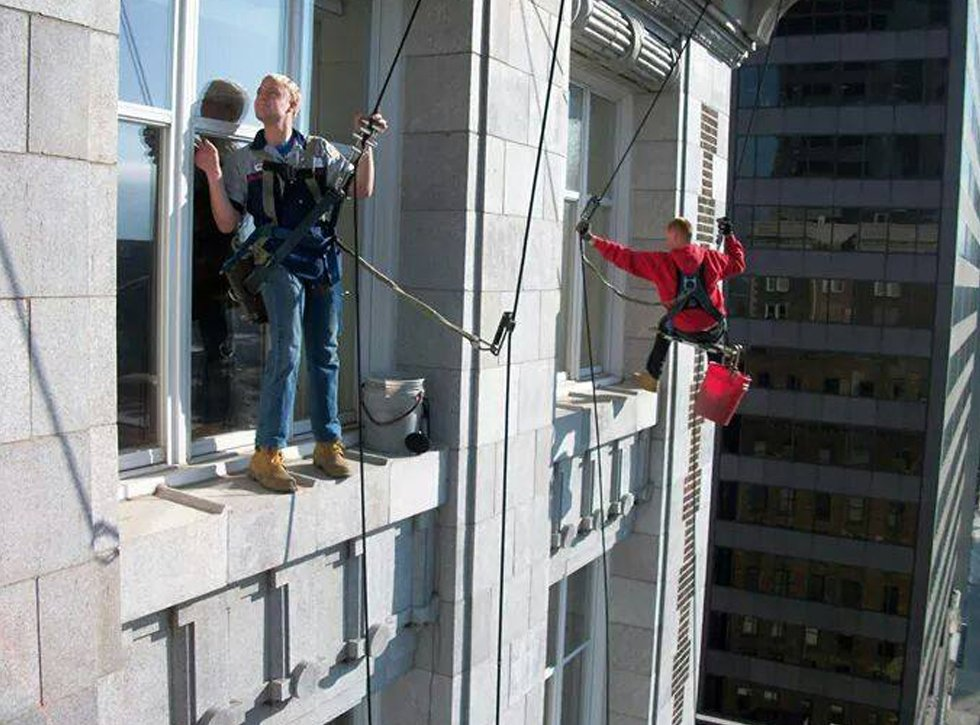 Window cleaners cleaning outside of widows on downtown building