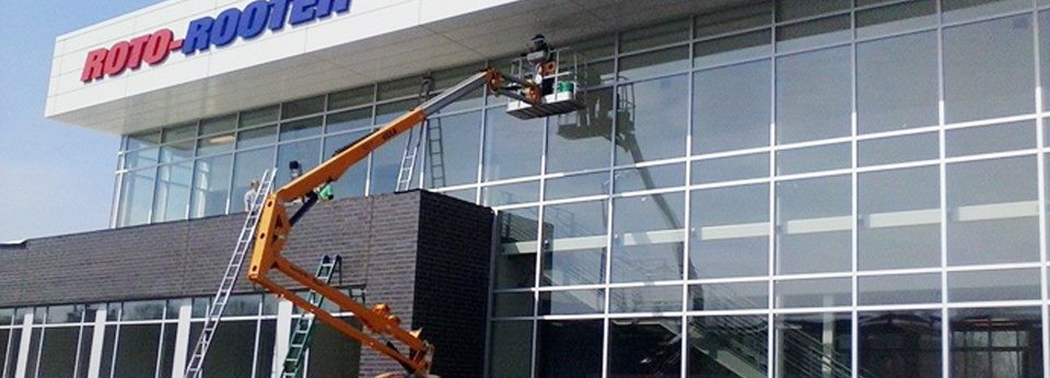 Workers in cherry picker cleaning windows on outside of office building