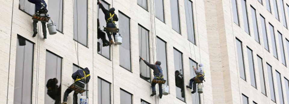Window cleaners working from rope and harness on outside office building windows