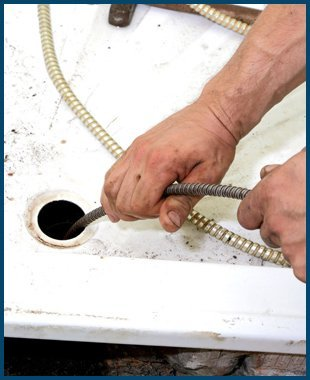 Plumber cleaning the drain