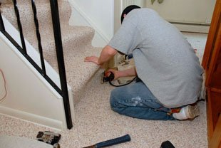 man installing carpet on stairs