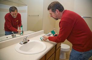 Plumber fixing bathroom sink