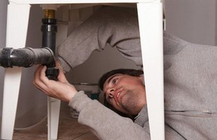Man fixing pipe under the sink