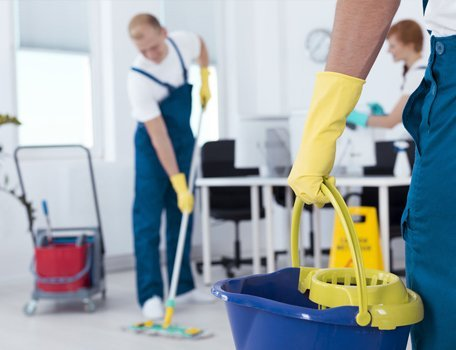 person holding mop pail and man cleaning floor