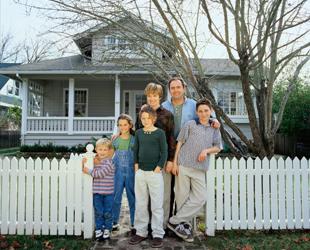 A View Of Family Standing In Front Of Home