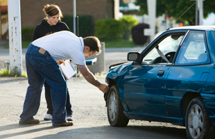 Man Making An Estimate For An Auto Insurance