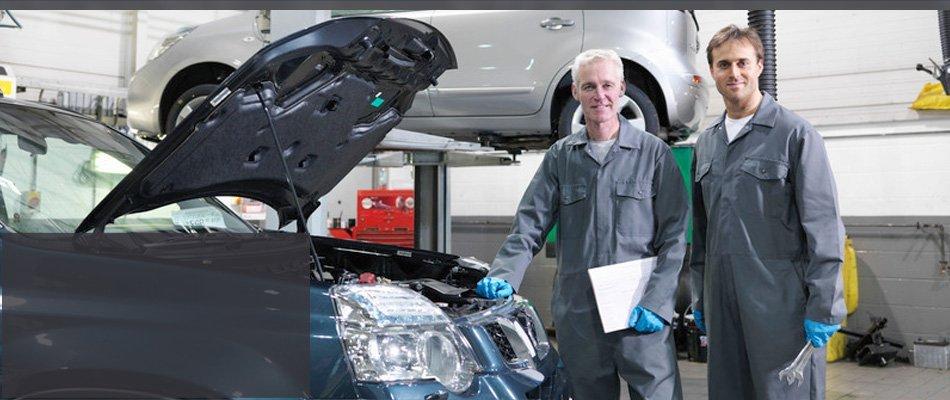 Two mechanic repairing SUV engine