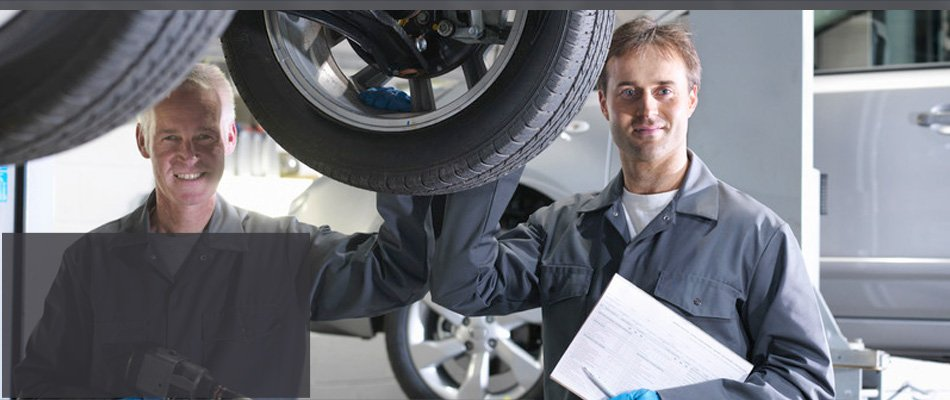 Two mechanic smiling with car tire