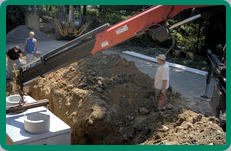 Construction workers installing white septic tank