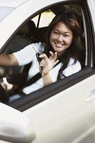 Woman in a car holding the car keys