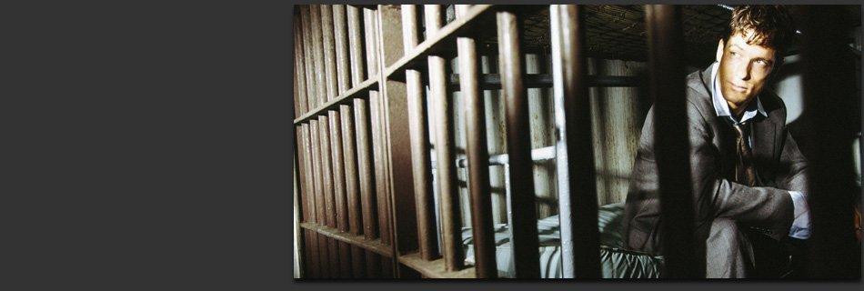 Man inside a dark prison cell