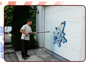 Guy washing graffiti off a garage