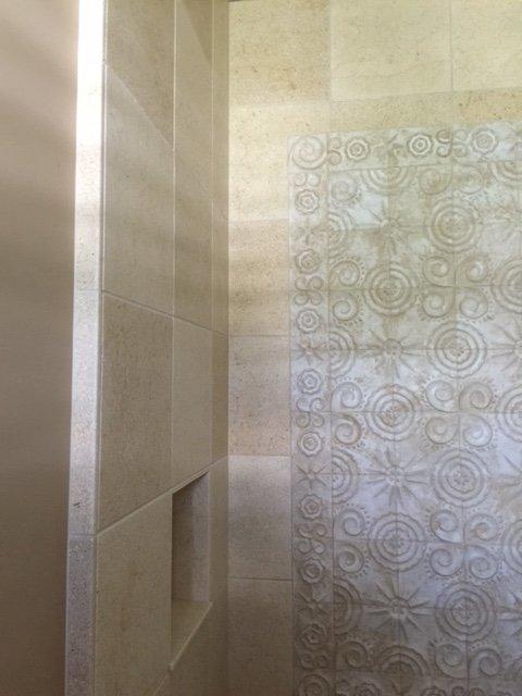 Tiled bathroom shower stall with custom splashwall