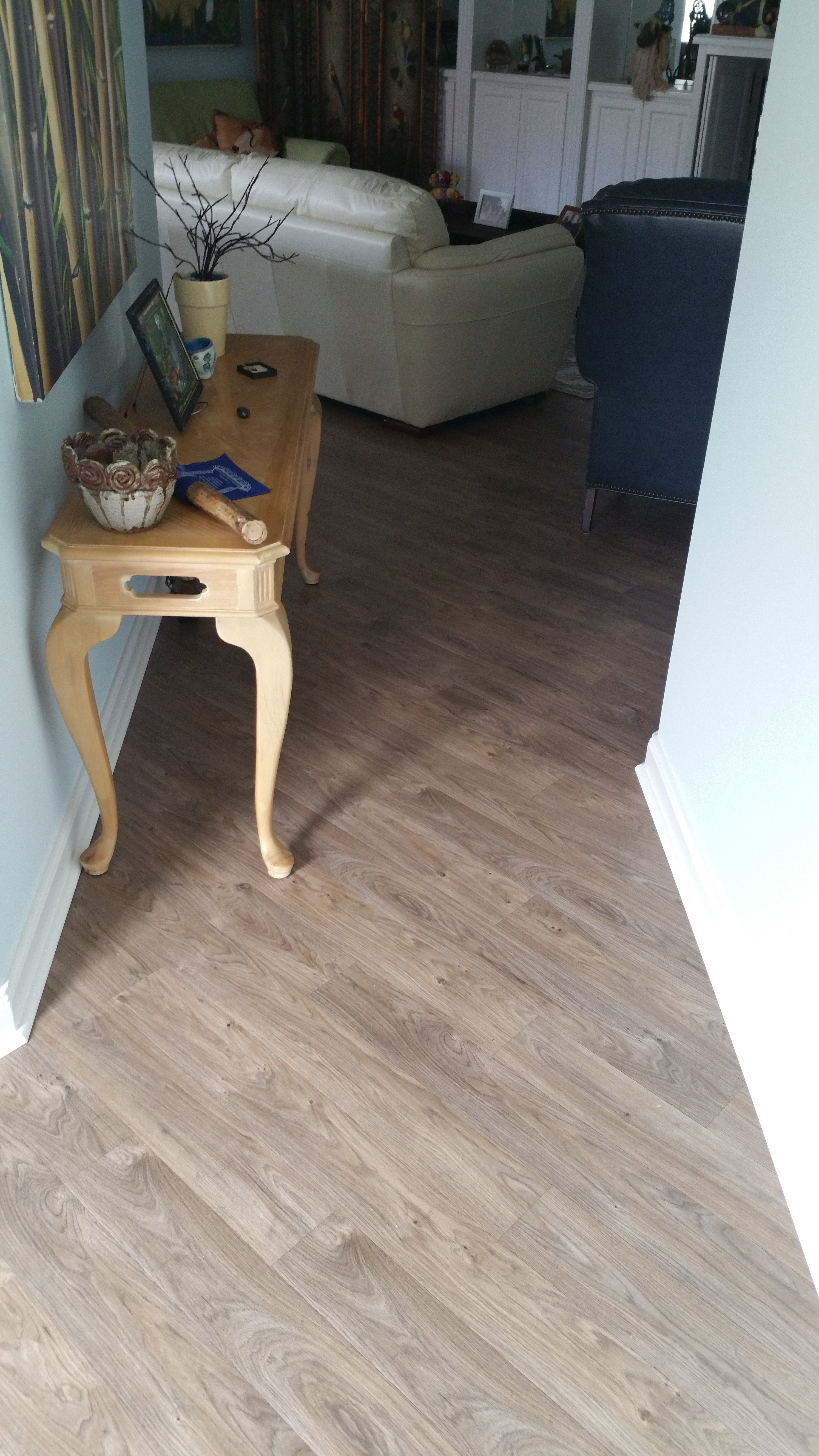 bleached walnut colored hardwood set at angle to hallway with side board holding photos, etc