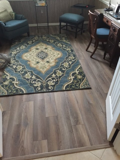 imitation hardwood laminate flooring in office with small area rug in greens, yellows, and turqoise