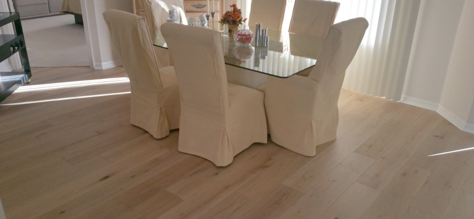 Pale hardwood floor in a dining room with glass top table and chairs with white cover