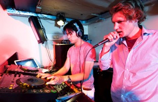 A DJ and a mc in action at a party in a nightclub