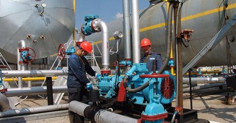 Two men working on refinery machines
