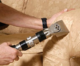 close-up of hand-held vacuum attachment cleaning arm of couch