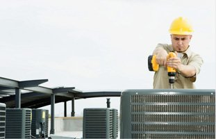 Technician wearing hard hat installing a cooling system