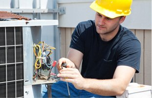 Technician wearing hard hat repairing the AC