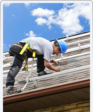Man installing rails for metal panels on residential house roof