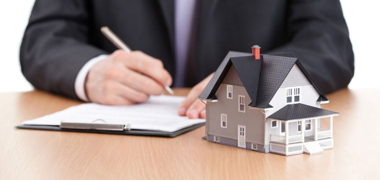 Businessman writing on a paper with a house architectural model