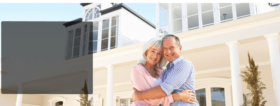 Senior couple with their property behind them