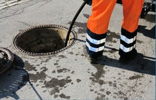 The man on the orange pants is cleaning the sewer
