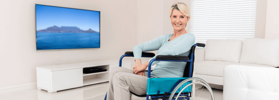 woman in wheelchair in a white living room smiling at camera