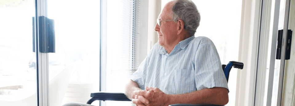 Elderly man in a wheelchair smiling out a window