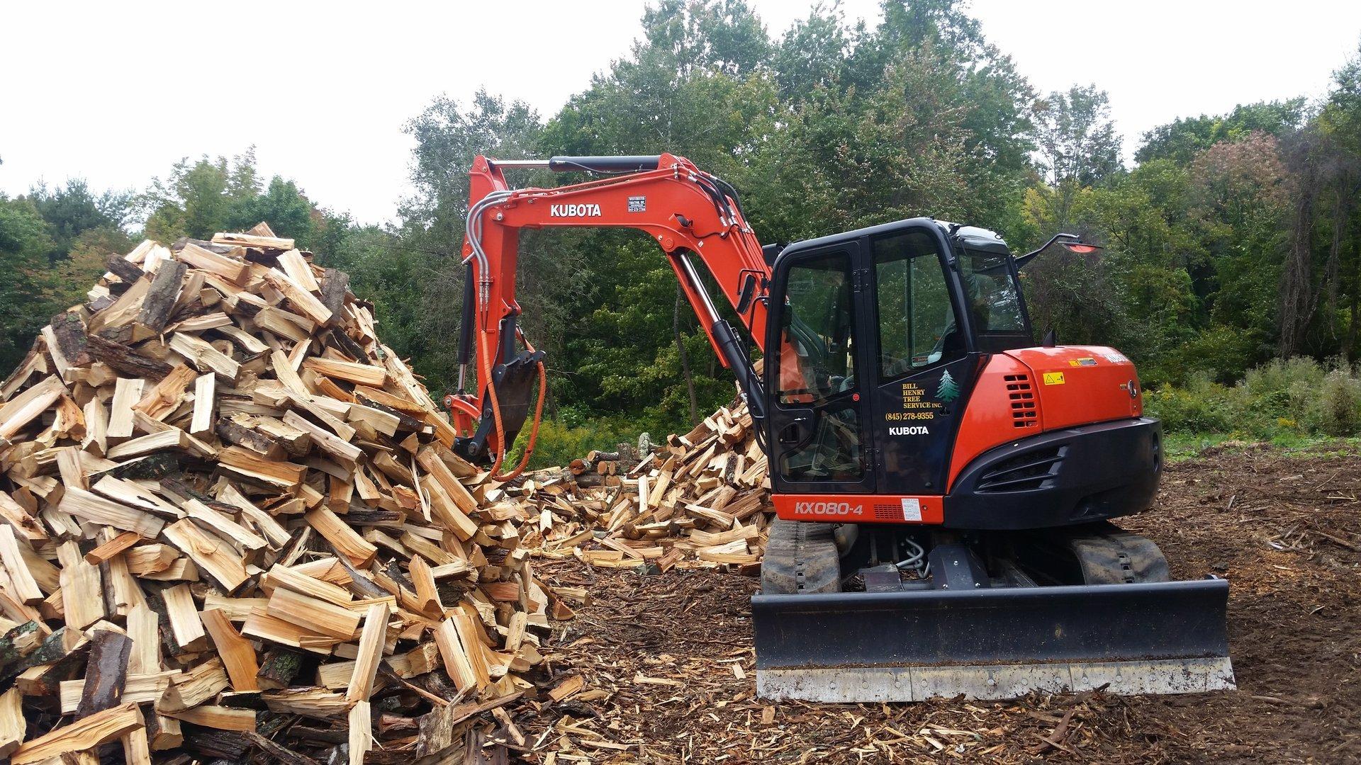 machine grabbing logs on pile