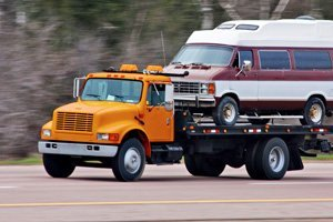 Rollback bed towing a car on the road