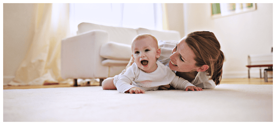 Happy mother and baby on carpet