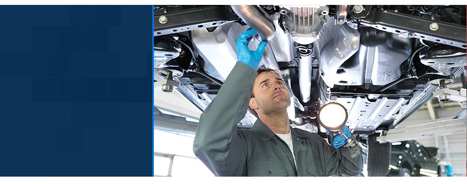 Male mechanic repairing auto underneath