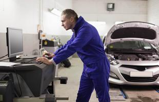 Repair man using a computer to repair car