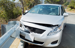 Front of silver car collided with steel fence