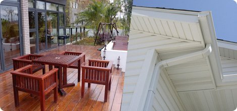 Functional wood deck and white residential gutter and downspout
