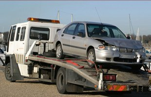 Tow truck carrying a sedan